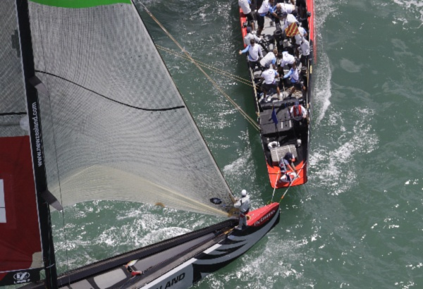 Team Origin hits the wands on the transom of BMW Oracle Racing during the pre start of day two of racing of Round Robin Two - PhotoBOB GRIESER Outsideimages.co.nz