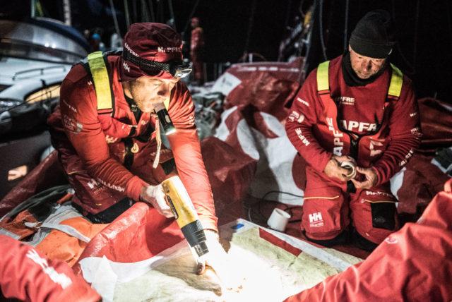 """Volvo Ocean Race 2018 - Leg 7, Tag 12 - Antonio """"Neti """" Cuervas-Mons, boat captain und Vorschiffmann von MAPFRE wärmt den Kleber für die Reparatur des Großsegeln an - Photo © Ugo Fonolla / VOR"""